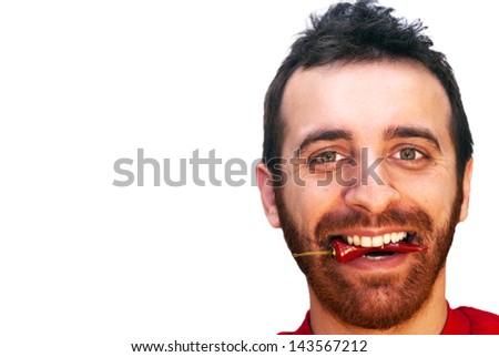 Young caucasian man with a red hot chili pepper in his mouth - stock photo