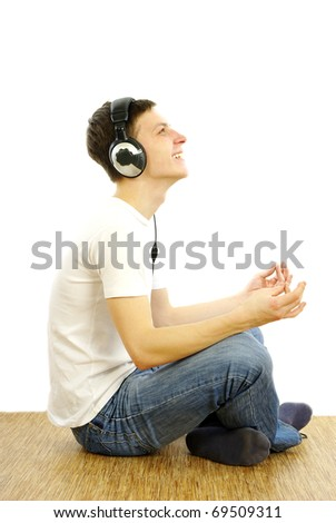 Young caucasian man with headphones  sitting in yoga pose and listening music. - stock photo