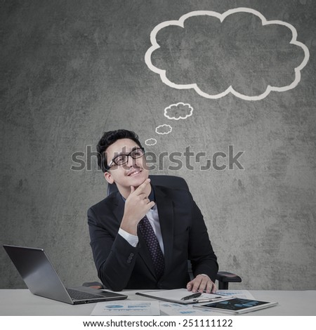 Young caucasian manager daydreaming while looking at empty cloud tag - stock photo
