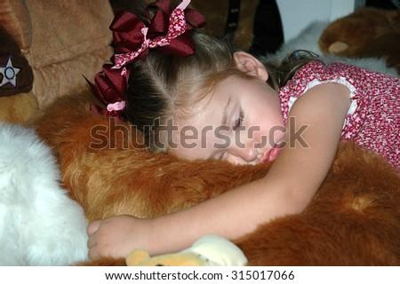 young caucasian preschool girl sleeping on a pile of stuffed animals on the floor - stock photo
