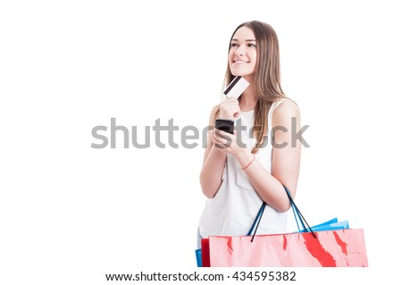 Young caucasian shopper with credit card and smartphone thinking what to buy isolated on white background with copyspace - stock photo