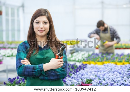 Young caucasian smiling women posing in nursery garden, with arms crossed.Female florist working in green house. - stock photo