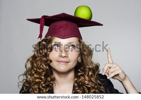 Young caucasian student with an apple on her head - stock photo