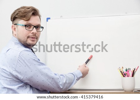 Young caucasian teacher pointing on whiteboard with marker. Education background. Text space - stock photo