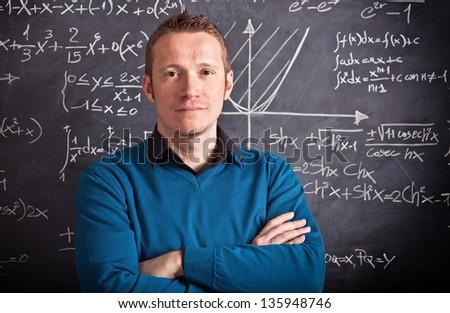 young caucasian teacher portrait with blackboard background - stock photo