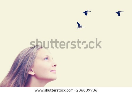 Young caucasian teenager girl looking upwards at flying birds. Image done with a vintage retro instagram filter - stock photo
