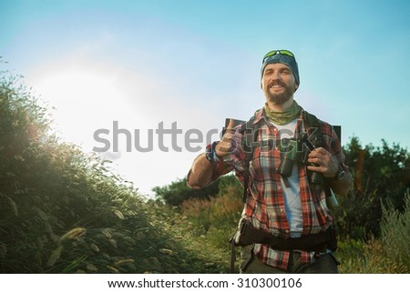 Young caucasian tourist with backpack walking on a green meadow at sunset