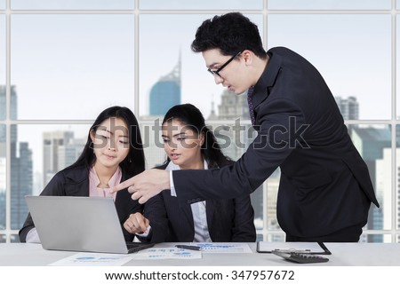 Young caucasian trainer pointing at laptop to explain a job on his employees in the office