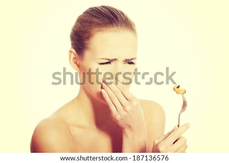 Young caucasian woman eating seafood with disguise. Isolated on white. - stock photo