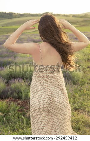 Young caucasian woman enjoying the view of a lavender field - stock photo