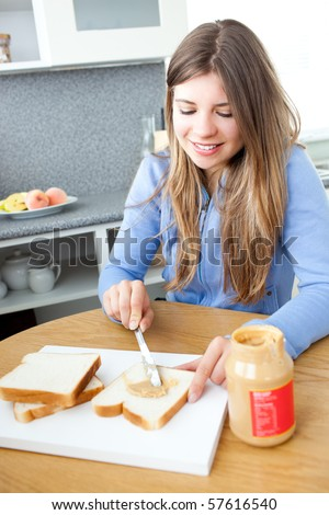 Young caucasian woman greasing peanut butter on her bread