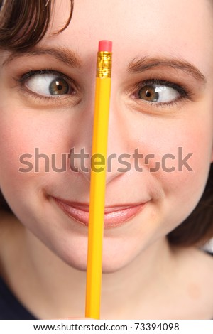 Young caucasian woman having fun going cross eyed with a pencil holding on her nose. - stock photo