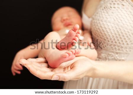 Young caucasian woman holding newborn son - stock photo