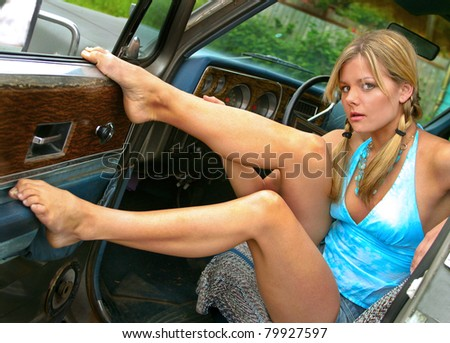 Young caucasian woman in denim shorts sitting in a truck. - stock photo