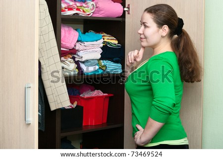 Young caucasian woman in the wardrobe packs things on a shelves.