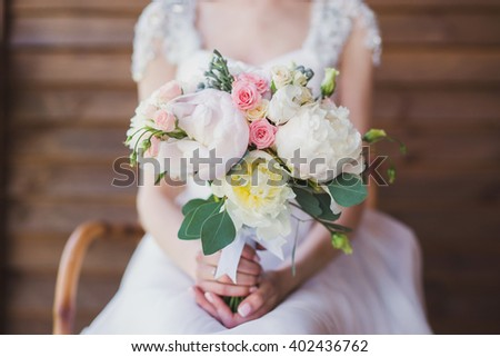 young caucasian woman in white wedding dress holds a beautiful bouquet of peonies in her hands - stock photo