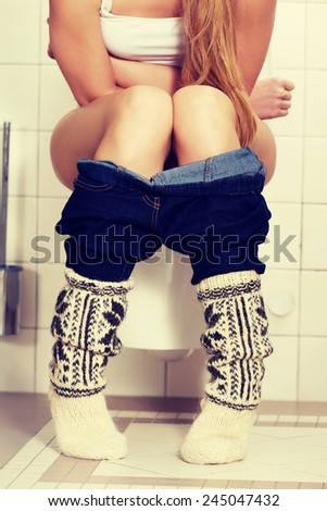 Young caucasian woman is sitting on the toilet, urinary bladder problem. - stock photo