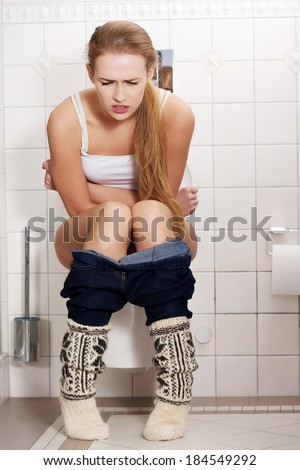Young caucasian woman is sitting on the toilet. urinary bladder problem or pregnancy or sickness concept. - stock photo