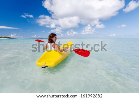 Young caucasian woman kayaking in sea at Maldives  - stock photo