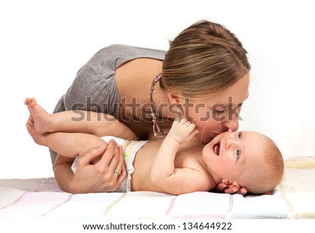 Young Caucasian woman kissing her baby son - stock photo