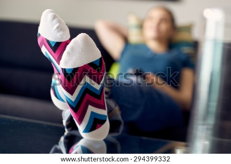 Young caucasian woman laying on sofa with colourful socks. She puts her feet on table and relaxes. The girl watches TV and holds remote control. Focus on socks - stock photo
