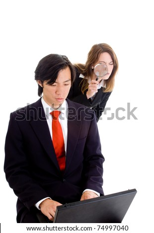 Young Caucasian woman peering over the shoulder of an Asian businessman with a magnifying glass.  Industrial espionage theme - stock photo