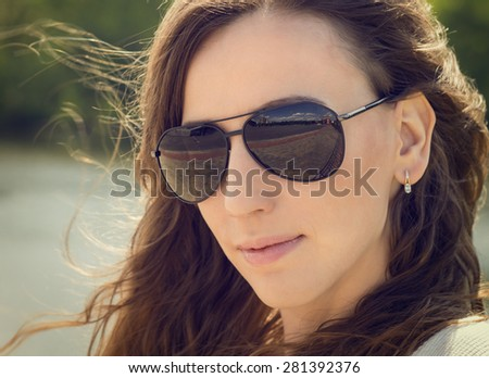 Young caucasian woman portrait with copy space. Warm color toned image of pretty girl in dark glasses - stock photo