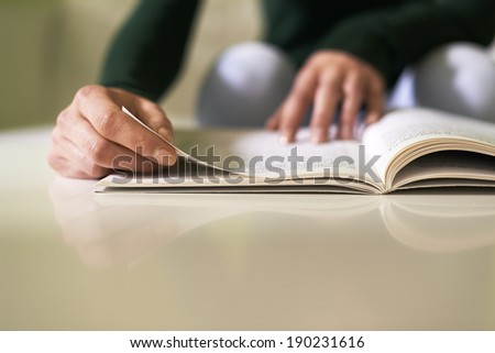 young caucasian woman reading book at home, sitting on sofa. Copy space on table - stock photo