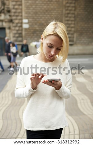 Young caucasian woman sending text message with her mobile phone in city, charming hipster girl chat on smart phone standing in urban setting, lost female tourist connecting to wireless for navigation - stock photo