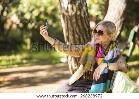 Young caucasian woman smiling for a self-portrait (selfie) on her smartphone, sitting on bench in the Park. - stock photo