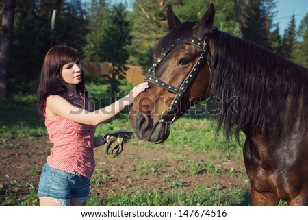 Young caucasian woman stroking a purebred brown horse