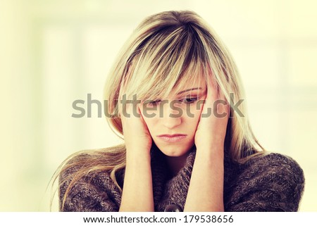 Young caucasian woman (student or businesswoman) with severe Migraine Headache holding hands to head - stock photo