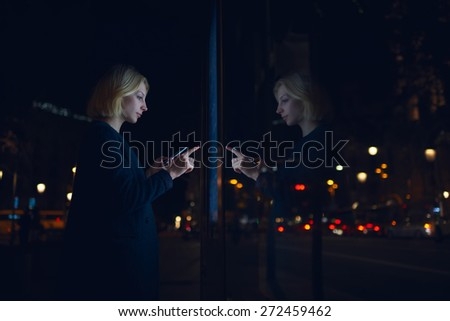 Young caucasian woman touching sensitive screen of smart city bus stop in night city with out-of-focus lights, female doing internet money payment with automated teller machine holding mobile phone - stock photo
