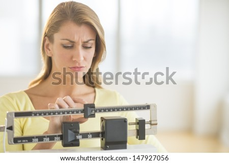 Young Caucasian woman using balance weight scale at gym - stock photo