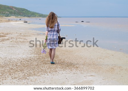 Young Caucasian woman walking along a beach with flowers