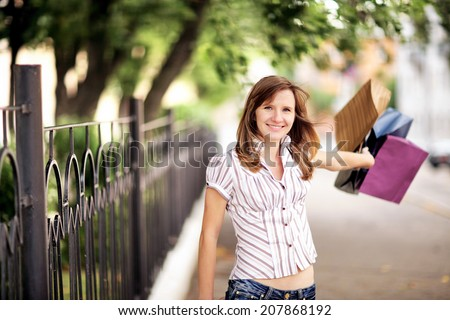 Young caucasian woman walking on the street with shopping bags.  - stock photo