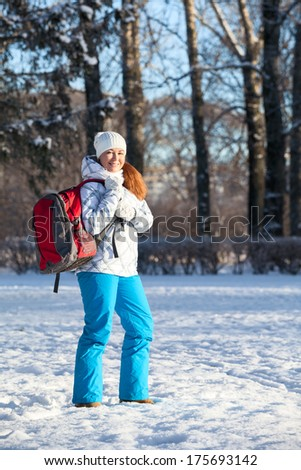 Young Caucasian woman walking with backpack in winter park - stock photo