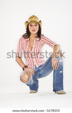 Young Caucasian woman wearing cowboy hat crouching and looking at viewer. - stock photo