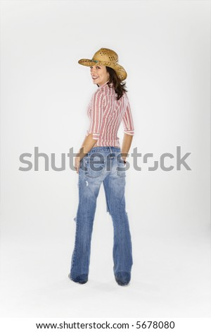 Young Caucasian woman wearing cowboy hat looking over shoulder at viewer and smiling. - stock photo