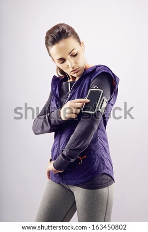 Young caucasian woman wearing earphones listening to music on mp3 player. Female runner listening music on grey background - stock photo