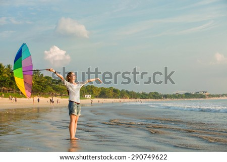 Young caucasian woman wearing white sunglasses with colourful rainbow umbrella enjoing beach time on Jimbaran beach on Bali before sunset. Travel, holidays, vacation, healthy lifestyle, tranquility - stock photo