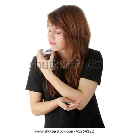 Young caucasian woman with glass of water taking pills,isolated on white background - stock photo