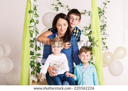 Young Caucasian woman with two babies having fun while sitting on swing - stock photo