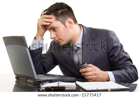 Young Caucasian worried businessman, with a laptop and cell phone - stock photo