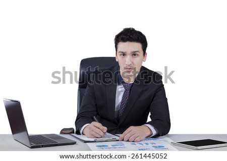 Young caucasian writes on paperwork while looking at the camera, isolated over white