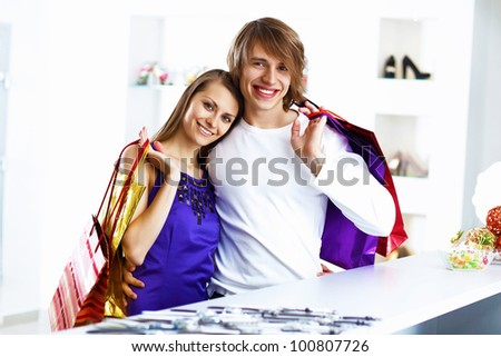 Young caucausian couple with bags doing shopping together