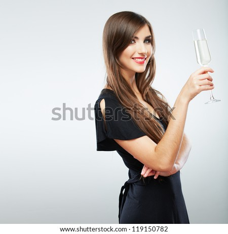 Young celebrating woman black dress . Beautiful model portrait isolated over studio background hold wine glass. - stock photo