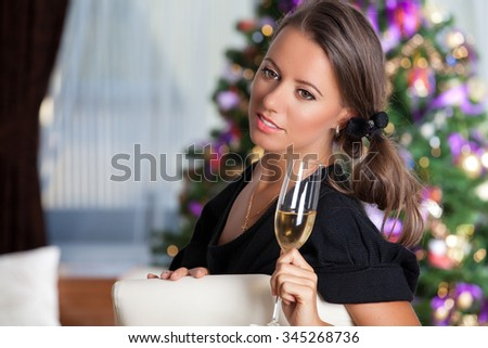 Young celebrating woman in black. Portrait of a gorgeous brunette with glass of sparkling wine over christmas tree lights background. Party, drinks, holidays, luxury and celebration concept. - stock photo