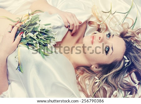 Young charming blonde holding in the hands of snowdrops - stock photo