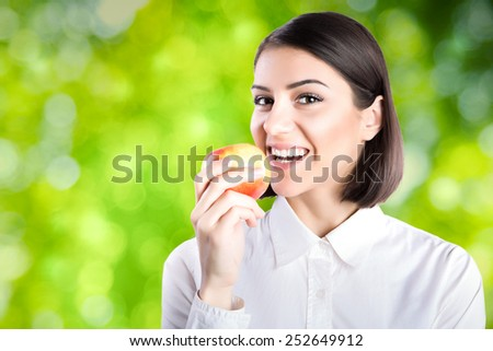 Young charming brunette woman biting apple with green nature background.Woman in white shirt eating apple,business woman eating healthy snack.Corporate woman on break eating healthy and organic - stock photo